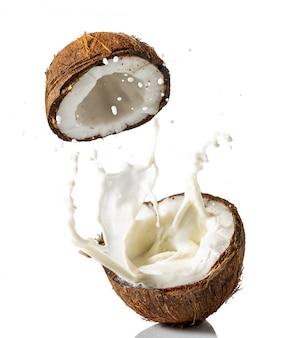 Gebroken kokosnoot met een scheutje melk op een witte achtergrond
