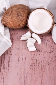 Gebroken kokosnoot met servet op houten achtergrond