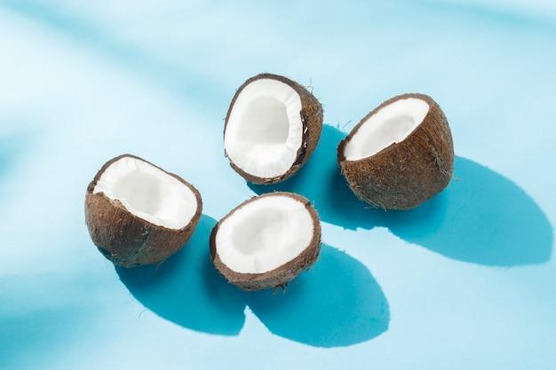 Gebroken kokosnoot op een blauwe ondergrond onder natuurlijk licht met schaduwen. hard licht. concept van voeding, gezond eten, rust in de tropen, vakantie en reizen, vitaminen.