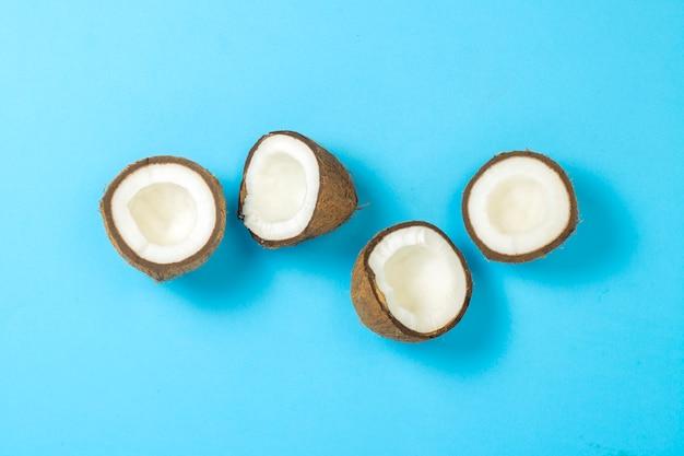 Gebroken kokosnoot op een blauwe ondergrond. plat lag, bovenaanzicht.