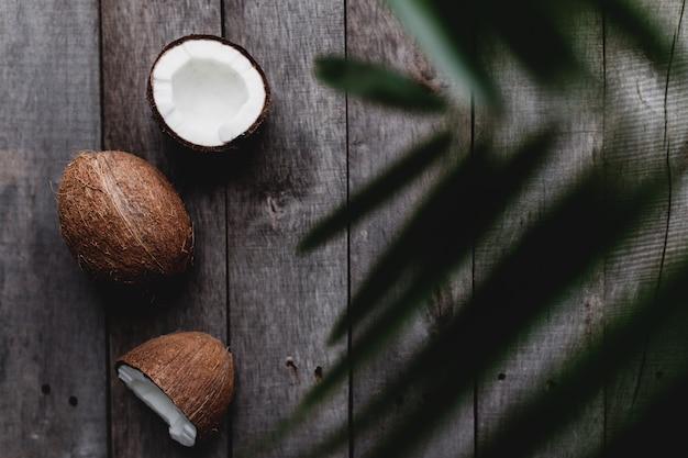 Gebroken kokosnoten op grijze houten achtergrond met palmblad. witte kokospulp. hoge kwaliteit foto