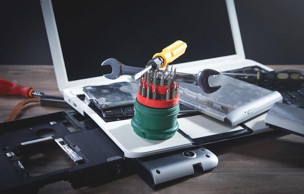 Gebroken laptop met een moersleutel en schroevendraaier op tafel. computerreparatieservice