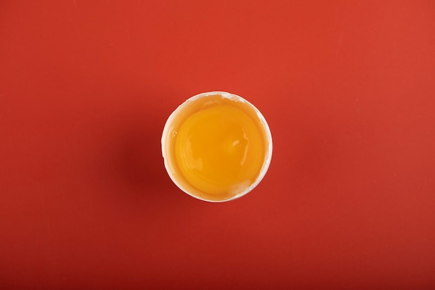 Gebroken organisch ei op rood oppervlak.