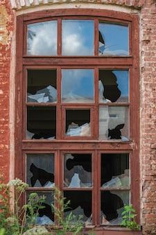 Gebroken ramen van een oud rood bakstenen gebouw