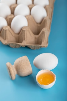 Gebroken rauw ei en container met eieren op blauwe ondergrond.