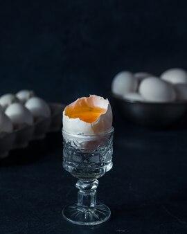 Gebroken rauw ei met dooier in glazen houder op donkerblauwe tafel