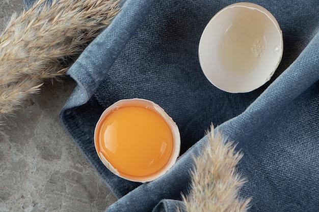 Gebroken rauw ei op marmeren oppervlak met tafellaken