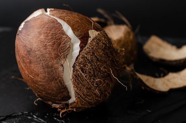 Gebroken rauwe kokosnoot op zwart. dieet en vegetarisch voedselconcept.