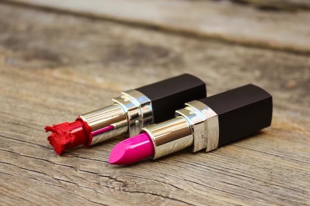 Gebroken rode en nieuwe roze lippenstiften op oude houten achtergrond.