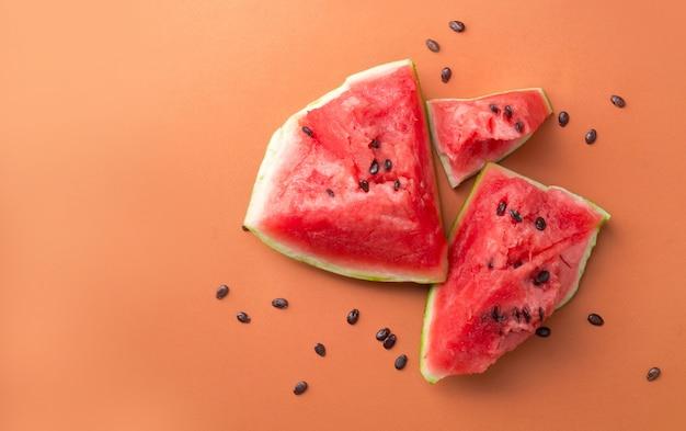 Gebroken rode rijpe watermeloen met stenen in de buurt van het over oranje oppervlak