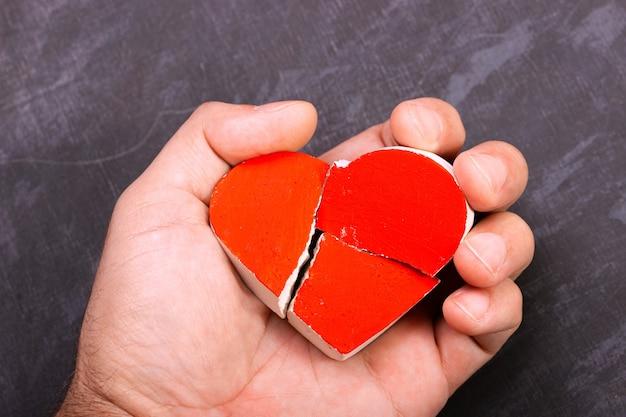 Gebroken rood hart in de hand van een man