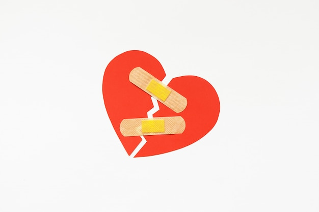 Gebroken rood hartsymbool met medisch flard, liefdeconcept. genezing. copyspace