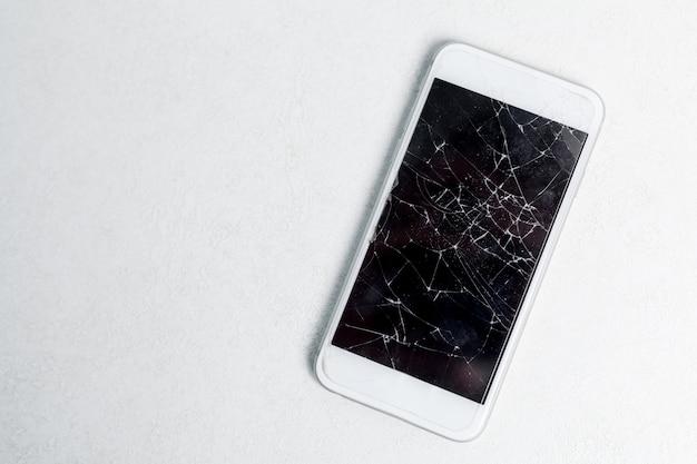 Gebroken scherm van mobiele telefoon, verspreide scherven.