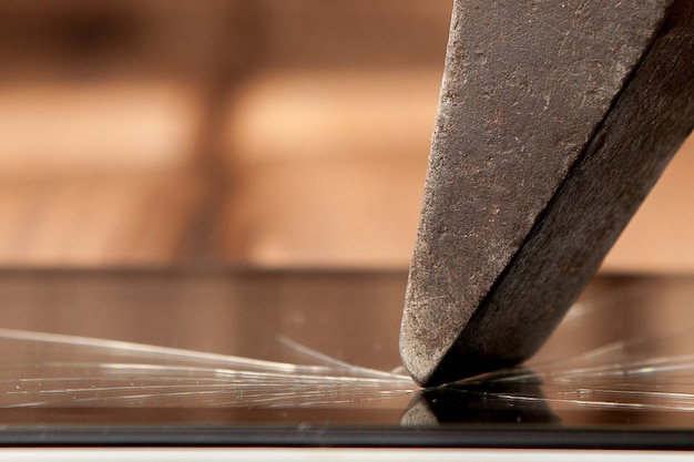 Gebroken scherm vernield gebroken glas close-up met hamer
