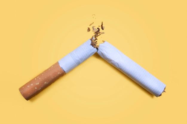 Gebroken sigaret die op gele achtergrond wordt geïsoleerd. niet roken concept