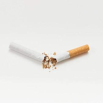 Gebroken sigaret die op witte achtergrond wordt geïsoleerd