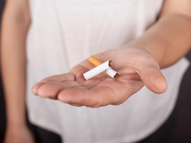Gebroken sigaret in een vrouwelijke hand, stoppen met roken, nicotineverslaving.