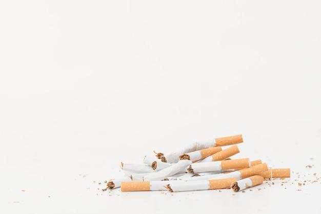 Gebroken sigaretten die op witte achtergrond worden geïsoleerd