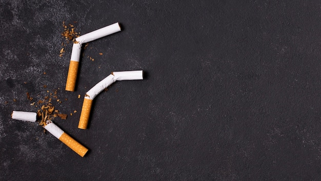 Gebroken sigaretten op gipspleisterachtergrond