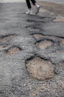 Gebroken stoep kuilen in het asfalt grote en diepe gaten of kuilen