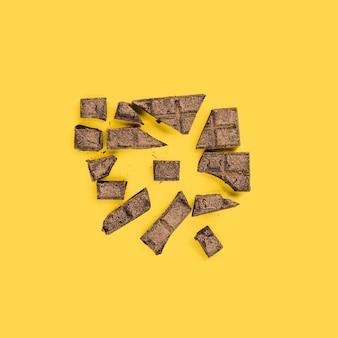 Gebroken stukjes chocolade op gele ondergrond
