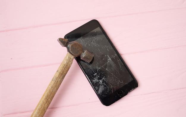Gebroken telefoonscherm op een tafel met een hamer