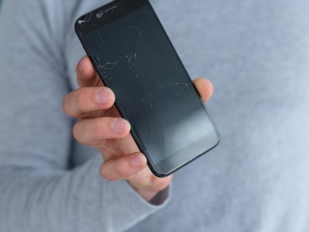Gebroken verbrijzeld gebarsten scherm. man met beschadigde slimme telefoon