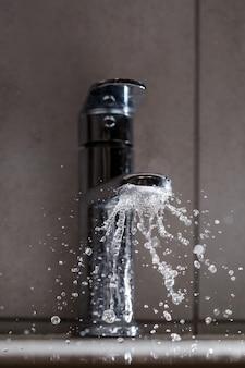 Gebroken waterkraan in de badkamer wastafel. water spat uit de zilveren kraan. selectieve focus