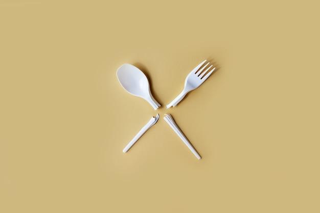 Gebroken wegwerp plastic vork en lepel op een uniforme achtergrond.