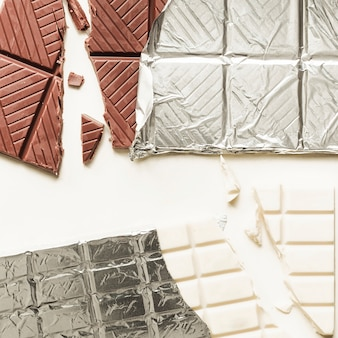 Gebroken witte en bruine chocoladereep gewikkeld in folie