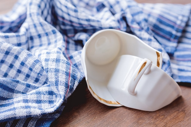 Gebroken witte kop met plaid blauwe handdoek