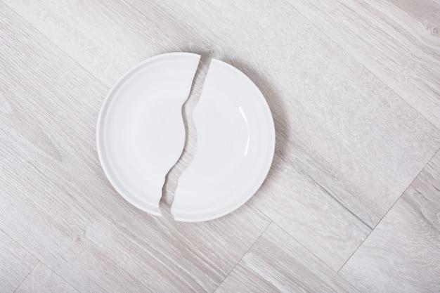 Gebroken witte plaat op wiooden het exemplaarruimte van het vloerbovenaanzicht