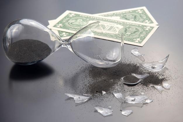 Gebroken zandloper en bankbiljetten. verlies van tijd en financiën. einde van verdienmogelijkheden. stop met het meten van uren. scherven van glas. zakelijke hoop verbrijzeld.