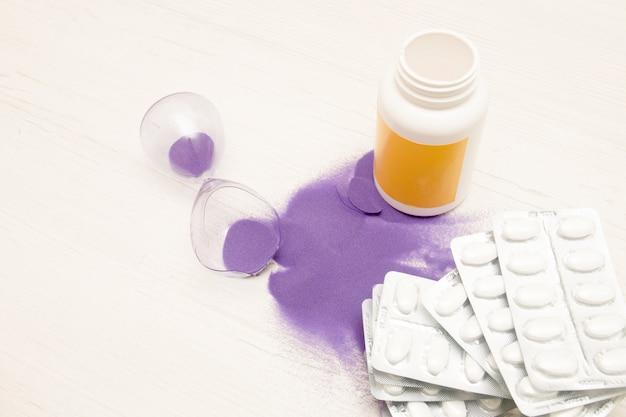 Gebroken zandloper en medicijnen op een lichte achtergrond