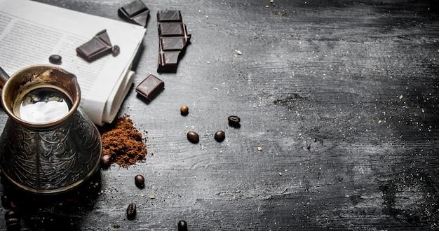 Gebrouwen koffiepot met verse krant en bittere chocolade op houten tafel.