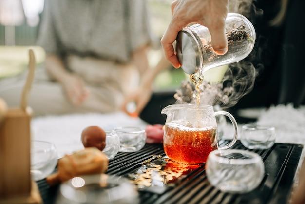 Gebrouwen rode thee wordt in een glazen theepot gegoten thee stoomt op een achtergrond van de zon