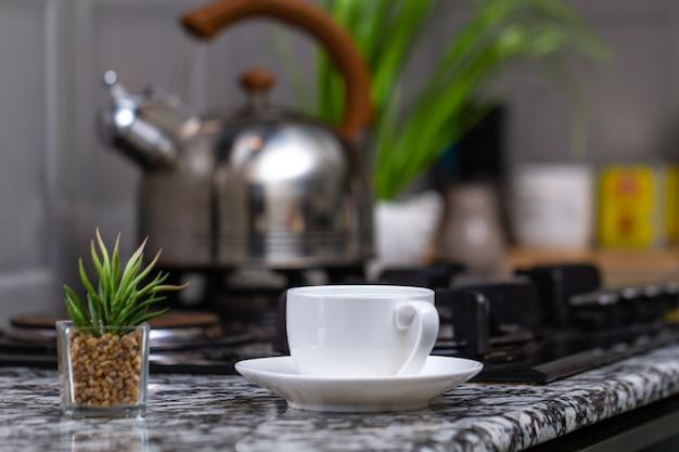 Gebrouwen thee in een witte kop en een fluitketel op gasfornuis in de keuken thuis. tijd voor ontbijt