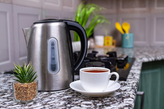 Gebrouwen thee in een witte kop en een waterkoker op de tafel in de keuken thuis. tijd voor ontbijt