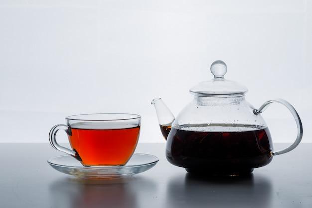 Gebrouwen thee in theepot en kopje zijaanzicht op een witte kleurverloop oppervlak