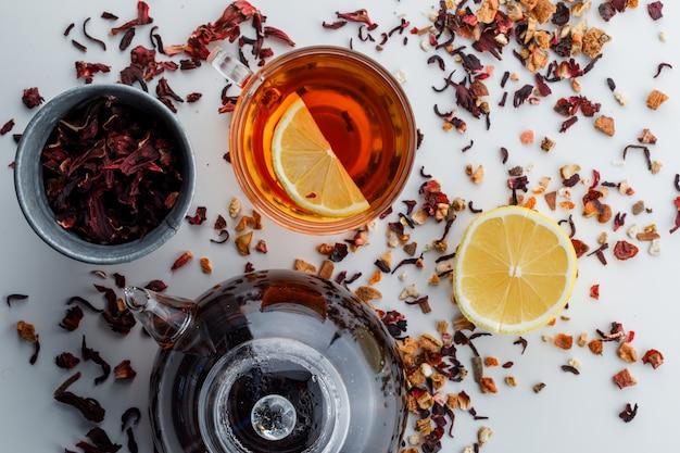 Gebrouwen thee met gedroogde kruiden, citroen in glas en theepot op wit oppervlak