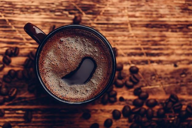 Gebrouwen zwarte koffie in metalen mok over houten oppervlak