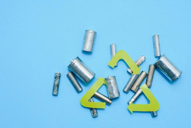 Gebruik aa en gooi batterijen die giftig zijn voor het milieu en vuil op de juiste manier weg tegen een groene achtergrond