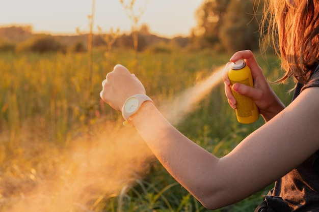 Gebruik buitenshuis anti-muggenspray tijdens een wandeltocht. close-up van jonge vrouwelijke backpackertoerist die insectenspray op handen toepast