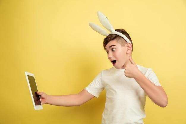 Gebruik de tablet, duim omhoog. blanke jongen als paashaas op gele studioachtergrond. gelukkige pasen-groeten.
