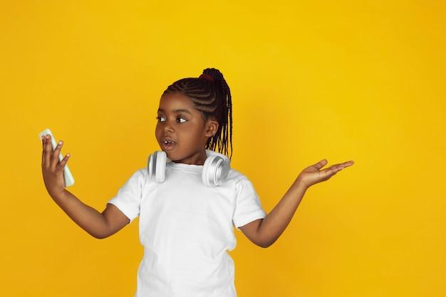 Gebruik de telefoon, luister naar muziek. het portret van een klein afrikaans-amerikaans meisje op gele studioachtergrond. vrolijke, mooie jongen. concept van menselijke emoties, expressie, verkoop, advertentie. kopieerruimte. ziet er schattig uit.