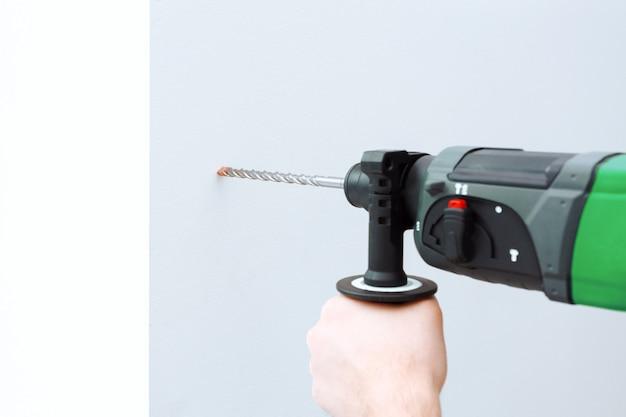 Gebruik een hamerboor om de muur te boren