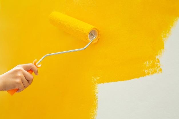Gebruik een roller om de slaapkamermuren geel te schilderen.
