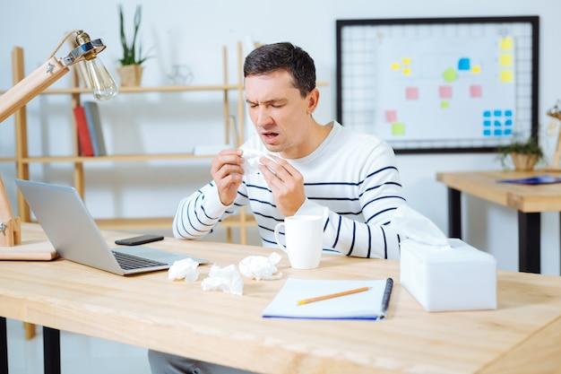 Gebruik een servet. gefrustreerde mannelijke persoon die mond openhoudt en ogen sluit tijdens het niezen