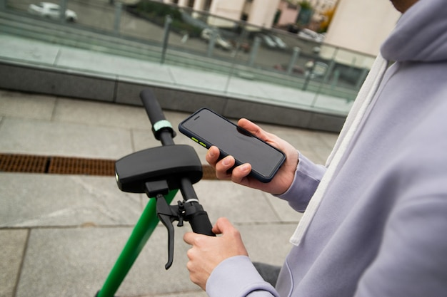 Gebruik je telefoon voor een comfortabele huur elektrische scooter. snel reisconcept. man in grijze hoody smartphone houden en kijken op online kaarten. groene e-scooter. voertuigen concept.