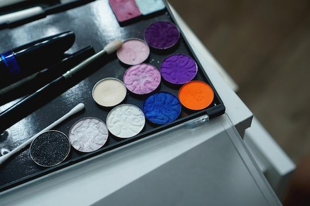 Gebruik palet van schaduwen voor make-up op een onscherpe achtergrond, close-up